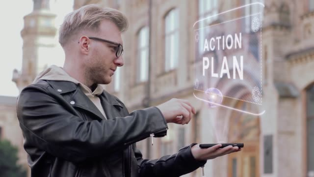 Smart young man with glasses shows a conceptual hologram of a Action plan