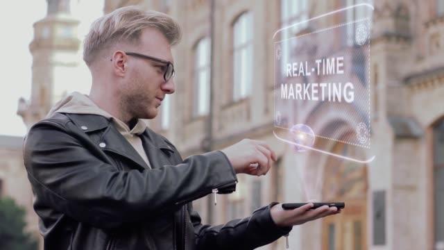 smart ung man med glasögon visar en begreppsmässig hologram realtid marknadsföring - realtid bildbanksvideor och videomaterial från bakom kulisserna