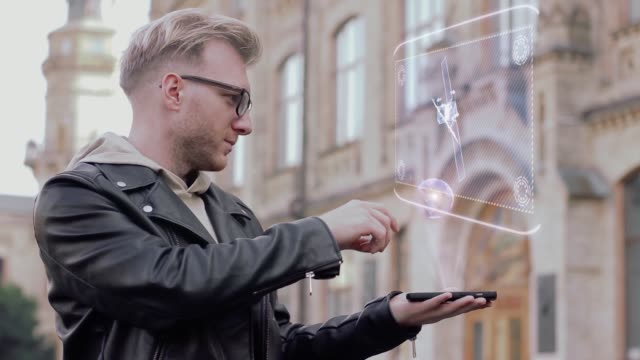 Smart young man with glasses shows a conceptual hologram satellite Smart young man with glasses shows a conceptual hologram satellite. Student in casual clothes with future technology mobile screen on university background positioning stock videos & royalty-free footage