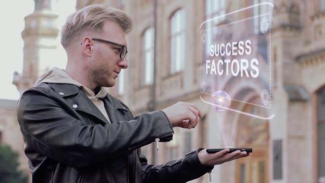 vídeos de stock, filmes e b-roll de jovem inteligente, com óculos mostra um holograma conceitual fatores de sucesso - manipulação digital