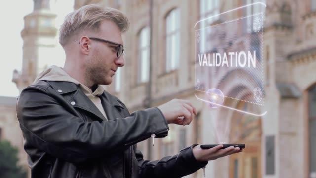 vídeos de stock, filmes e b-roll de jovem inteligente, com óculos mostra um holograma conceitual validação - validação