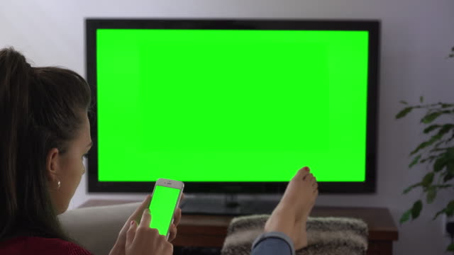 Smartphone and tv chromakey screens, young woman feet up. video