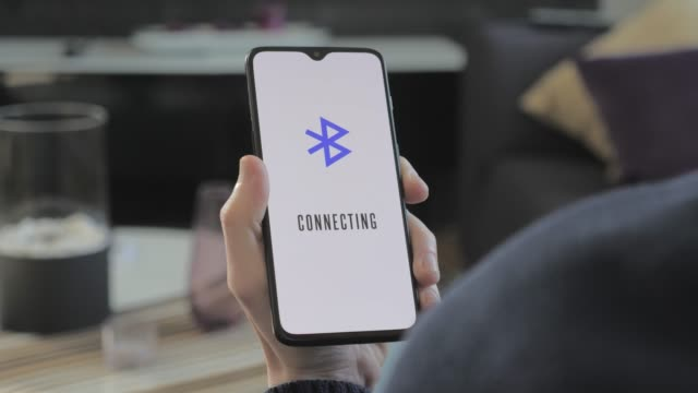 Smartphone connecting to bluetooth Over the shoulder view of man holding a modern smartphone connecting to bluetooth bluetooth stock videos & royalty-free footage