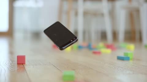 vídeos y material grabado en eventos de stock de slo mo smartphone cayendo al suelo y entre los bloques de juguete - caer