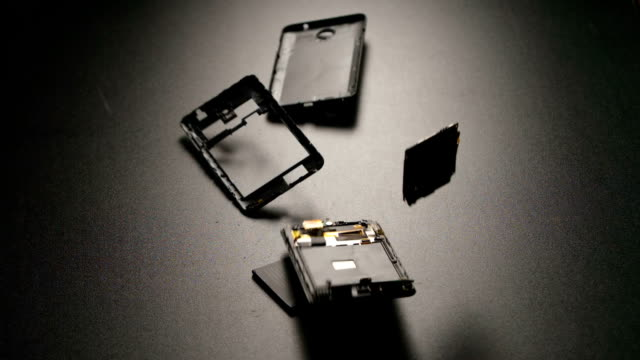 SLOW MOTION: Smartphone falls on a floor, breaks and a parts fly away video
