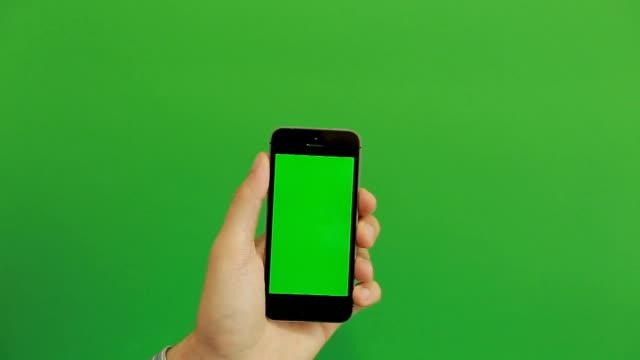 yeşil ekranda elle akıllı telefon - hand holding phone stok videoları ve detay görüntü çekimi