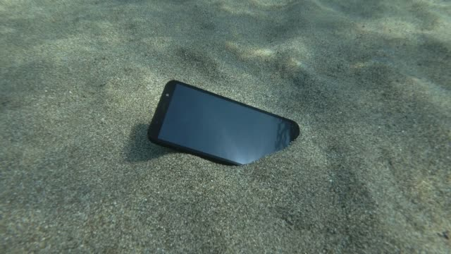 Smartphone lies on a cave seabed on its screen reflects the surface of blue water with small waves. Underwater view. Mediterranean Sea, Europe.