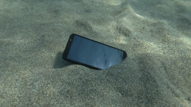 Smartphone lies on a caved seabed on its screen reflects the sun with rays and surface of blue water with small waves. Underwater view. Mediterranean Sea, Europe.