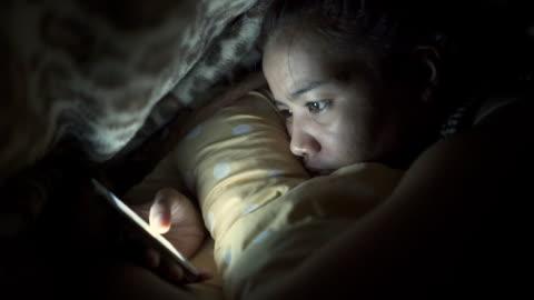 vídeos de stock e filmes b-roll de smartphone na cama - adolescente