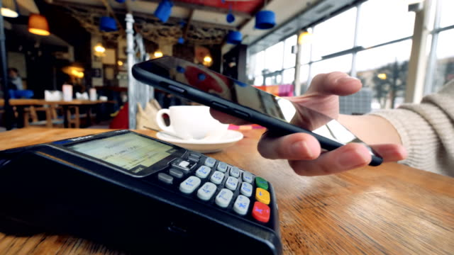 vídeos de stock e filmes b-roll de smartphone payment. female hand pay using nfc system and contactless card. - paying with card contactless
