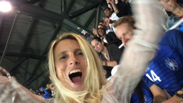 スタジアムで彼女の座席からジャンプし、彼女のチームを応援して女性のスマート フォン動画 - 応援点の映像素材/bロール