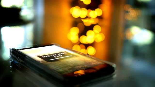 A Smartphone with an app installation screen with cinematic bokeh video