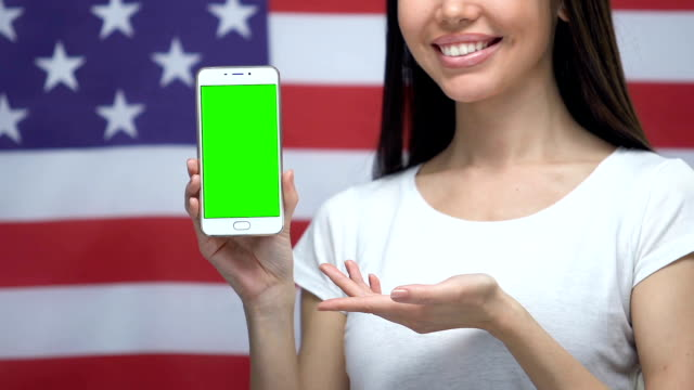 Smartphone with green screen in female hands, USA flag background, application