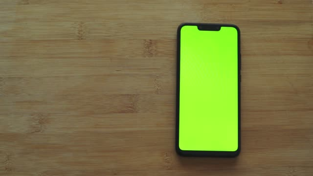 smartphone with green screen on wooden