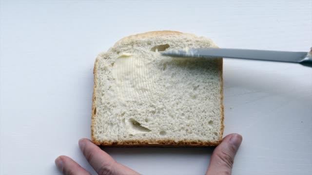 stockvideo's en b-roll-footage met boter smeren op wit brood met knif - fresh start yellow