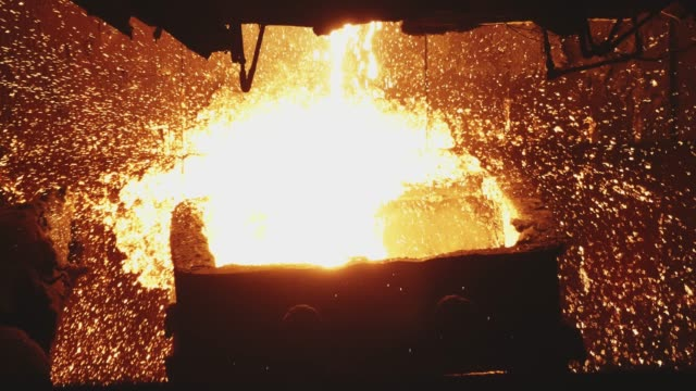 Smelting of the metal in the foundry at the steel mill. Close up for hot steel being poured from the furnace with many sparcles, iron industry.