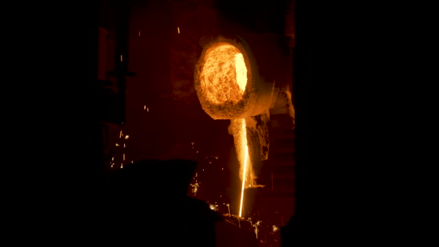 smelting works at plant. scene. jet of alloy is poured out and sparks are carried in different directions at smelter. bright hot stream of alloy flows and sparkles - attrezzatura energetica video stock e b–roll