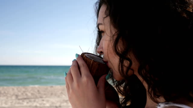 smile girl with curly hair on beach, woman drinks cocktail oconut, exoticism, summer season, background sea ocean and sand video