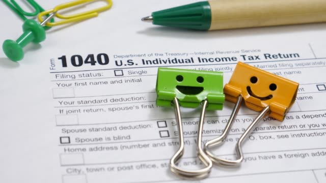 Smiles Binder Clips and Pen on 1040 Tax Form
