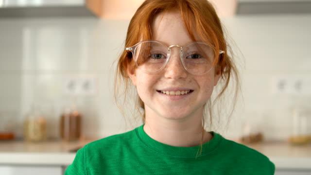 stockvideo's en b-roll-footage met smiley, sproetengezicht, roodharig meisje in oogglazen dat camera bekijkt, giechelt - bril brillen en lenzen