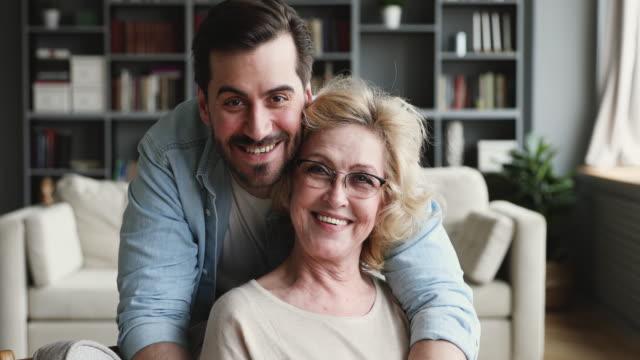 sorridente figlio degli anni '30 che guarda la telecamera che abbraccia la mamma più anziana al chiuso - figlio maschio video stock e b–roll