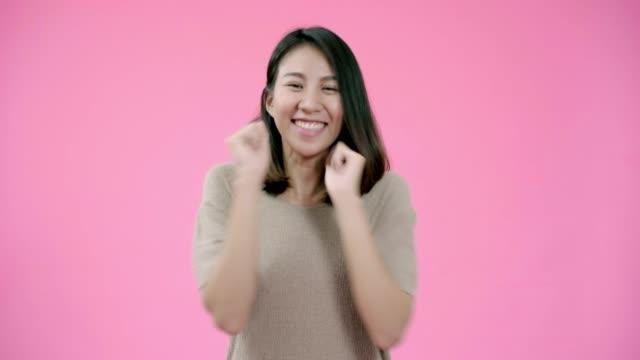 肯定的な表現で愛らしいアジアの女性を笑顔, 広く笑顔, カジュアルな服を着て、ピンクの背景の上にカメラを見て.ハッピー愛らしい嬉しい女性喜ぶ成功。 - スーパーモデル点の映像素材/bロール