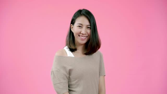 肯定的な表現で愛らしいアジアの女性を笑顔, 広く笑顔, カジュアルな服を着て、ピンクの背景の上にカメラを見て.ハッピー愛らしい嬉しい女性喜ぶ成功。 - スタジオ 日本人点の映像素材/bロール