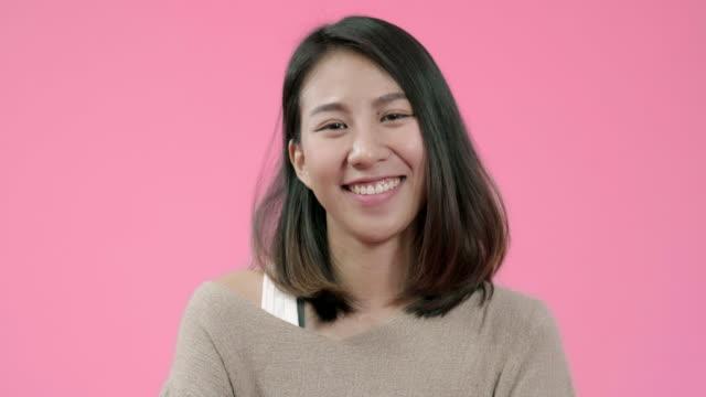 ポジティブな表情で愛らしいアジアの女性を笑顔、広く笑顔、カジュアルな服を着て、ピンクの背景上のカメラを見ています。幸せな愛らしい嬉しい女性が成功を喜ぶ。 - スタジオ 日本人点の映像素材/bロール