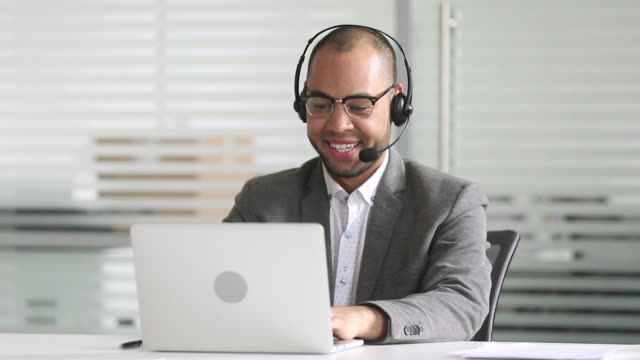 Smiling african american businessman manager talking by video conference call Smiling african american businessman manager talking by video conference call looking at laptop wearing headset, customers service support agent consult client on computer by business teleconference salesman stock videos & royalty-free footage