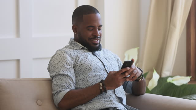 Smiling african american man holding smartphone texting at home
