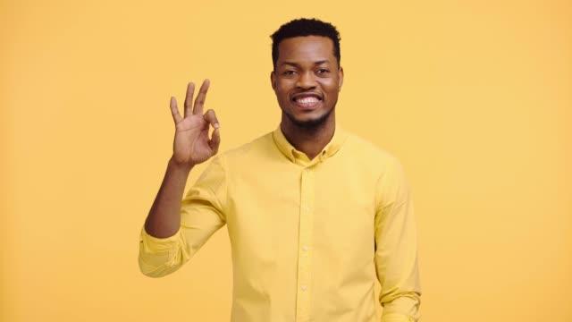 lächelnde afrikanische amerikanische mann zeigt okay zeichen isoliert auf gelb - farbiger hintergrund stock-videos und b-roll-filmmaterial
