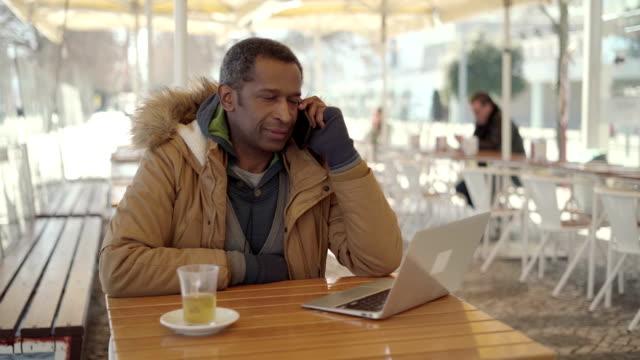 vídeos de stock e filmes b-roll de smiling african american man talking by smartphone in cafe - esplanada portugal
