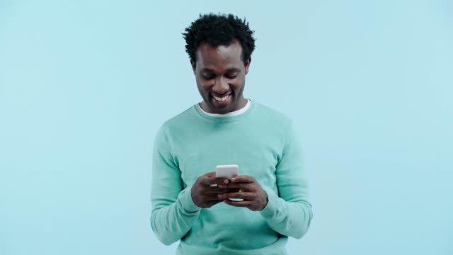 smiling african american man using smartphone isolated on blue - kolor tła filmów i materiałów b-roll