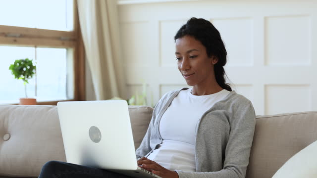 Smiling african lady sit on couch using laptop at home