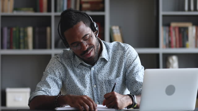 Smiling african male student wear headset elearning making notes