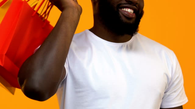Smiling african man with shopping bags showing thumbs up on yellow background