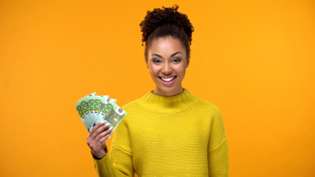 Smiling African-American lady showing bunch of euros to camera, high-paid job