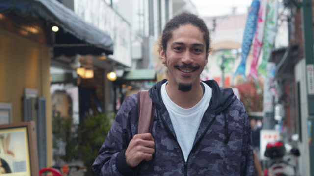smiling african-american man on japanese street - baffo peluria del viso video stock e b–roll