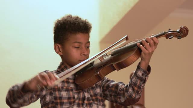 stockvideo's en b-roll-footage met glimlachend afro jongen speelt op viool. - christmas tree