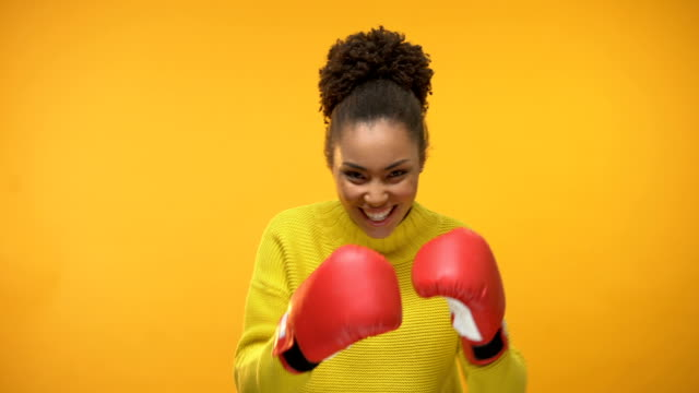 vídeos de stock e filmes b-roll de smiling afro-american girl in boxing gloves imitating fight, having fun, victory - remote work