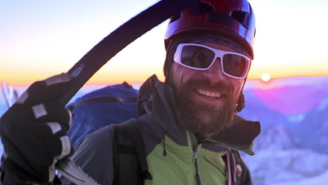 leende alpinist på den snöiga bergstoppen vid solnedgången - skägg bildbanksvideor och videomaterial från bakom kulisserna