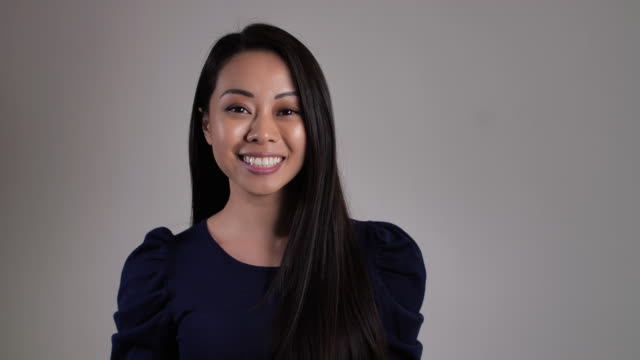미소와 카메라를 보고 아름 다운 아시아 여자 일반 회색 배경에서. - 20 29세 스톡 비디오 및 b-롤 화면