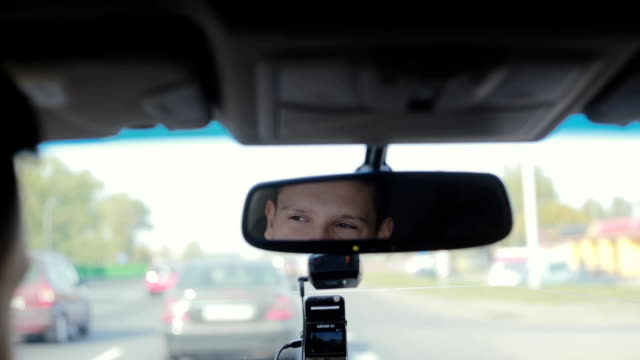 Smiling and talking man in a mirror while driving car on a busy road in a city. Handsome mans face. Traveling by car video