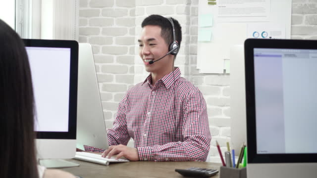 Smiling Asian man telemarketing customer service  agent talking to customers video