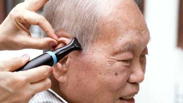 Smiling Asian senior man receiving a hair trimming