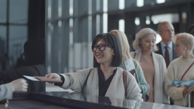 uśmiechnięta azjatka dająca dokumenty podróży agentowi odprawy na lotnisku - happy holidays filmów i materiałów b-roll