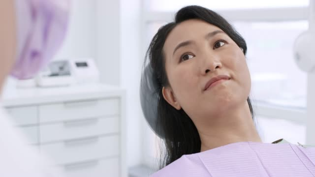leende asiatisk kvinna liggande i stolen och talar till hennes tandläkare - two dentists talking bildbanksvideor och videomaterial från bakom kulisserna