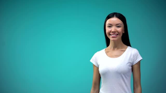 アジアの女性示す黄金カード カメラ, 無限クレジット, 銀行に笑みを浮かべてください。 - グリーティングカード点の映像素材/bロール