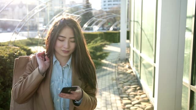 Smiling asian woman texting on smartphone outdoor video