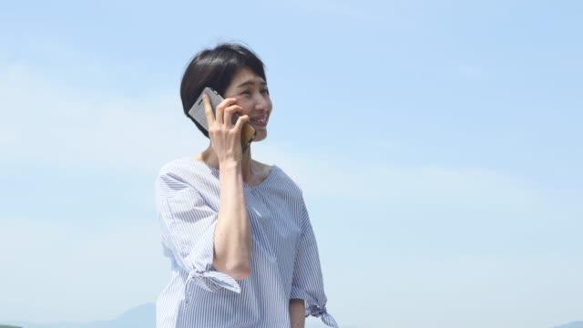 アジアの女性の笑顔 - 電話を使う点の映像素材/bロール